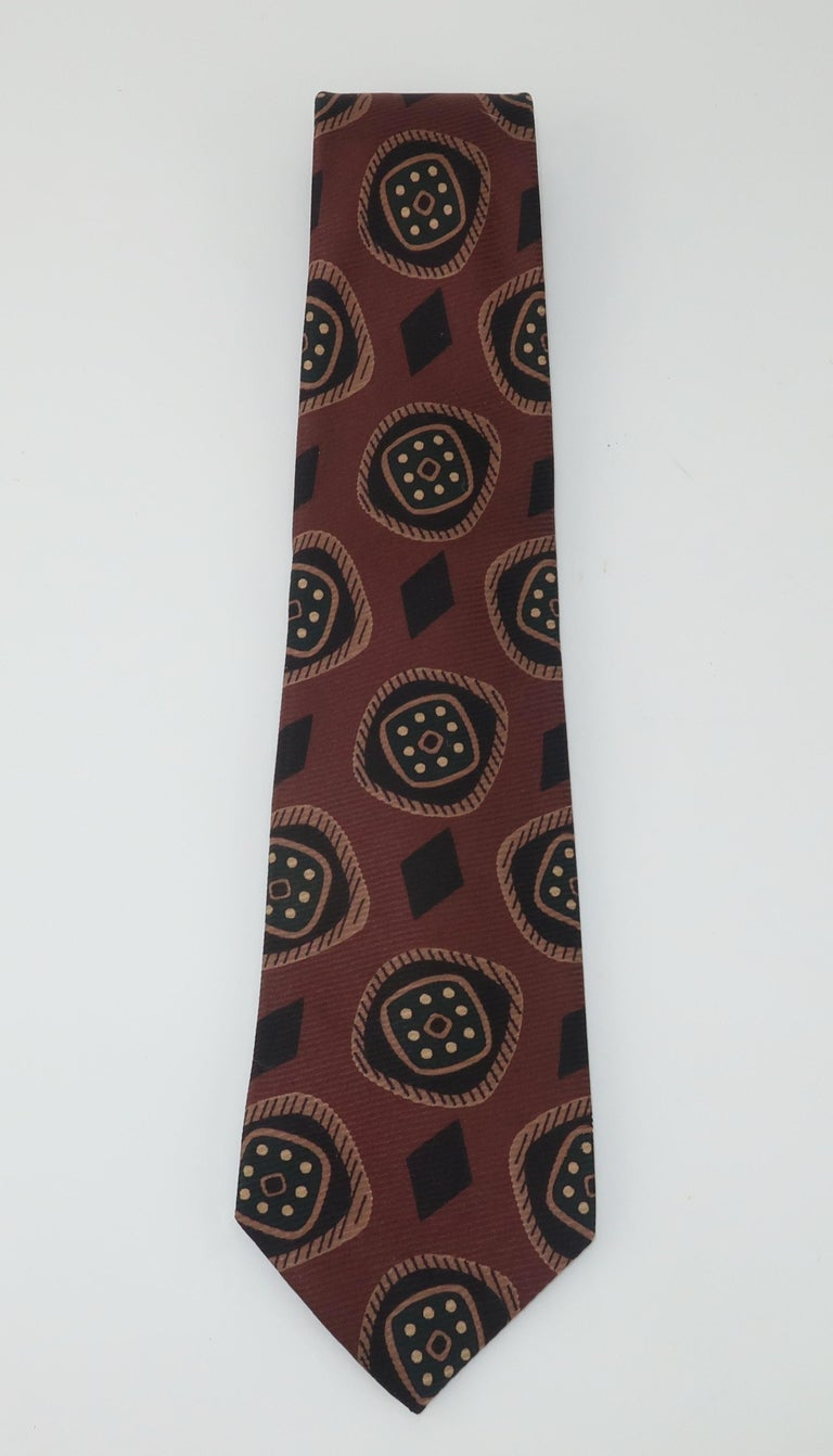 By British designer Hardy Amies (1909-2003), a dapper men's silk neck tie with a geometric pattern in shades of brown, black, tan and very dark green.  Mr. Amies was appointed as a Royal Dressmaker by Queen Elizabeth in the 1950's and enjoyed a
