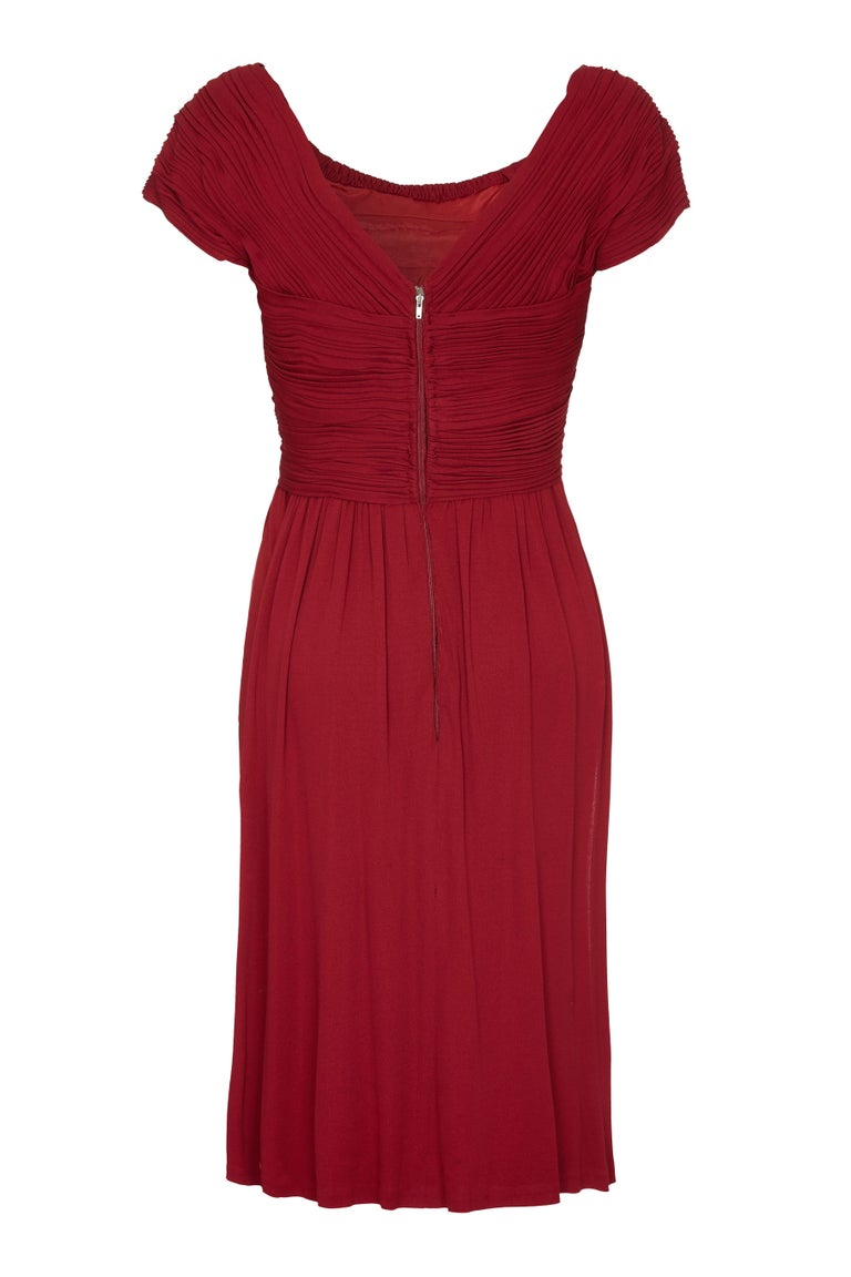 This gorgeous 1950s vintage Harrods boutique dress in deep burgundy showcases some exquisite tailoring with unique pleating on the bodice and sleeves. The simple line of the dress with its soft scoop neckline and cap sleeves is juxtaposed with