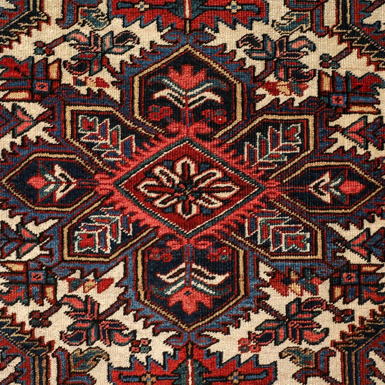 This vintage Heriz Persian carpet circa 1920s in pure wool and vegetable dyes is hand knotted using a Persian knot upon a cotton warp and weft. It features a brightly colored geometric floral medallion upon a cream-colored field, with a