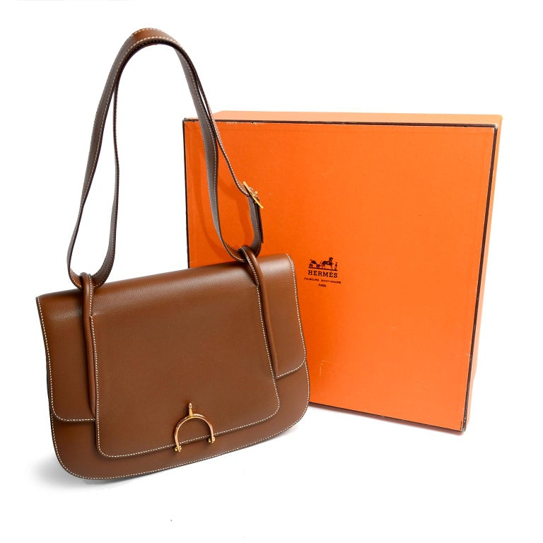 This is a beautiful vintage 1985 Hermes brown leather handbag that appears unworn.  We love the gold horse bit buckle and the color of the leather.  The bag comes with its original box - (weakened box corners) This timeless bag is 9