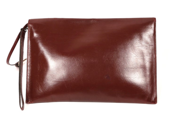 Bordeaux box leather pouchette with rich patina and gunmetal hardware including working lock and key made by Hermes dating to the late 1970's, early 1980's. Can be used for day or night. Pouchette measures 10