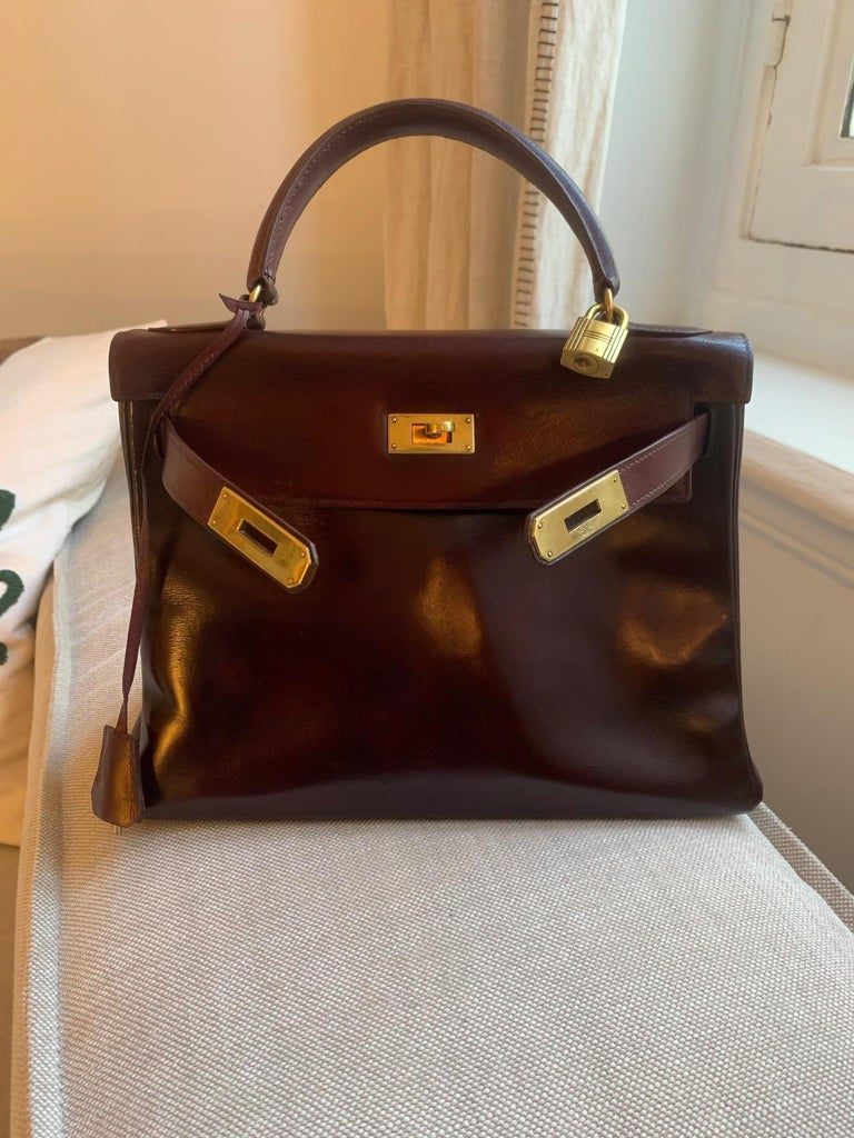 Beautiful VINTAGE Hermes Kelly 28 cm from 60's.  Burgundy calfskin handbag, gold plated metal hardware, burgundy leather handle for carrying.  Closure by flap. Lining in burgundy leather, one zippered pocket, two patch pockets. Signature: