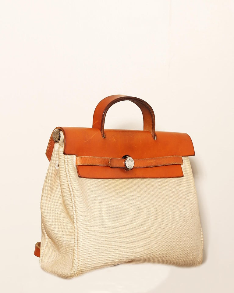 This authentic Hermes Herbag Zip Leather and Toile 39 showcases the brand's more subtle and care-free design perfect for everyday. Crafted in off-white toile and natural vache hunter leather details, this stylish and functional bag features an