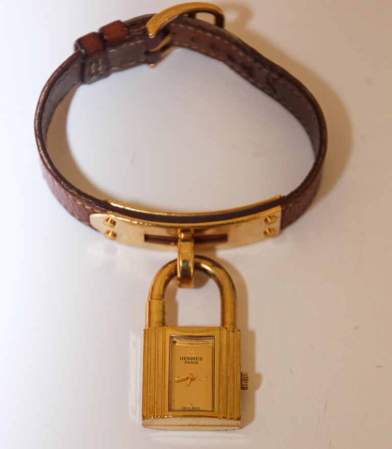 Vintage Hermes Kelly Watch. 1989 Hermes tan leather Kelly Watch gold plated. Removable gold plated lock charm watch which dangles from a gold-plated base on the strap. Hermes Kelly watch, stamped circle T from 1980.  Swiss made, signed push/pull
