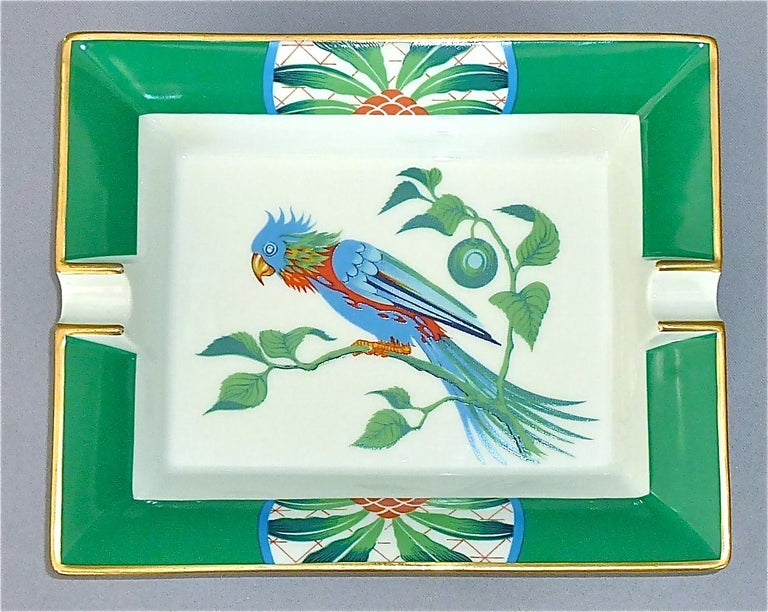 A fine and beautiful Hermès Limoges vintage oblong porcelain ashtray with parakeet bird motif, partly gilt, in colors green, blue and red. Marked Hermes Paris and Made in France to the side and suede covered to the base for protection. This ashtray