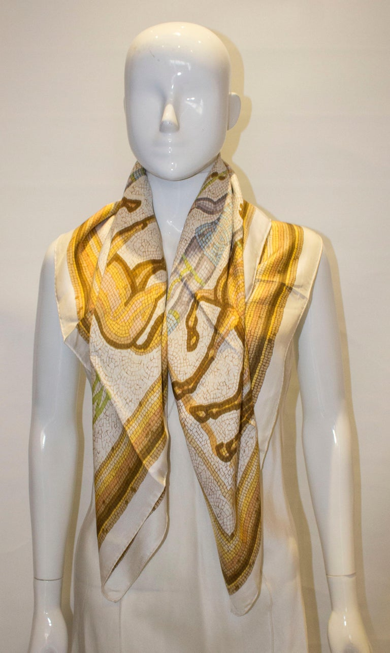 A chic vintage Hermes silk scarf with a horse design print., measuring 35'' square.