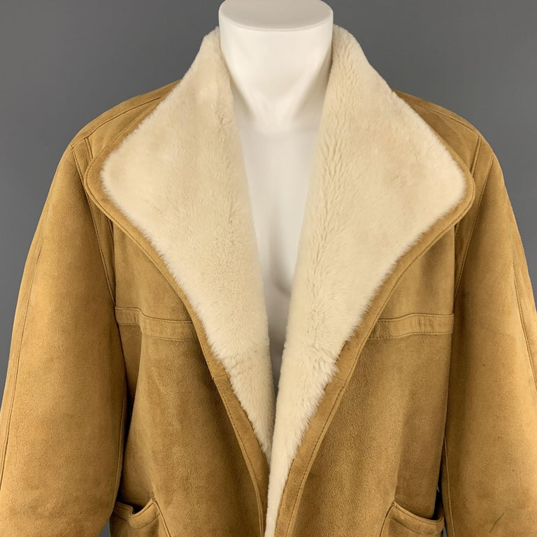 Vintage HERMES over coat comes in golden tan suede shearling with full cream trimmed fur interior and features a wide pointed collar, open front, and oversized patch pockets. Pen mark on sleeve. As-is. Otherwise excellent condition. Made in France.