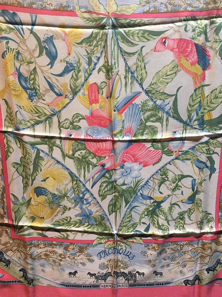 Vintage Hermes Tropiques Silk Scarf in Pink c1980s in good condition. Original silk screen design c1987 by Laurence Bourthoumieux features various tropical flora and fauna surrounded by a coral pink border. Zebras and giraffes in palm desert scenes