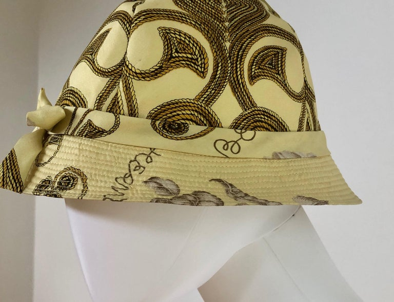 Offered is an Hermes Yellow, Gold and Ivory silk cloche / bucket hat with a dainty bow to the front center and a gold rope and floral theme.  Make:  Hermes (label reads Hermes Paris) Place of manufacture:  France Size:  58 (approximating) Color: