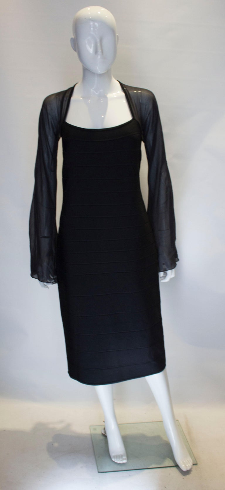 A chic Herve Leger dress  in black . This dress is unusual having long sleeves. It has a square neckline, and central back zip. The size has a some stretch.