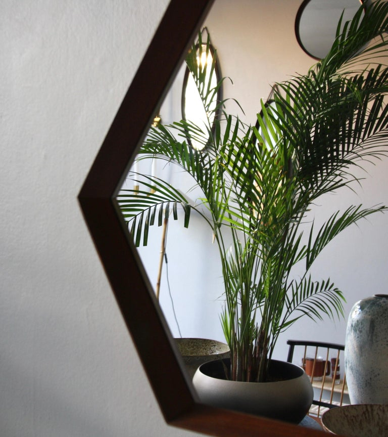 A vintage hexagonal wall mirror with string hanging strap, made in Denmark, circa 1950. The mirror is made of sections of solid teak wood which are joined together using finger joints. This exposed construction, the rope strap and the tapering of