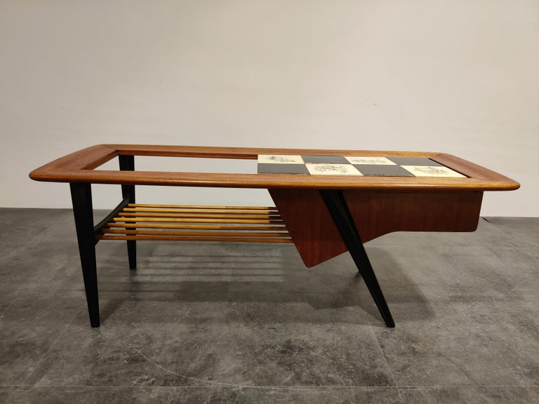 Midcentury coffee table by the Belgian designer Alfred Hendrickx.  The table features a hidden bar compartment and a moveable ceramic tyle top with drawings.  Beautifully finished wooden top and black lacquered legs.  One of our favorite