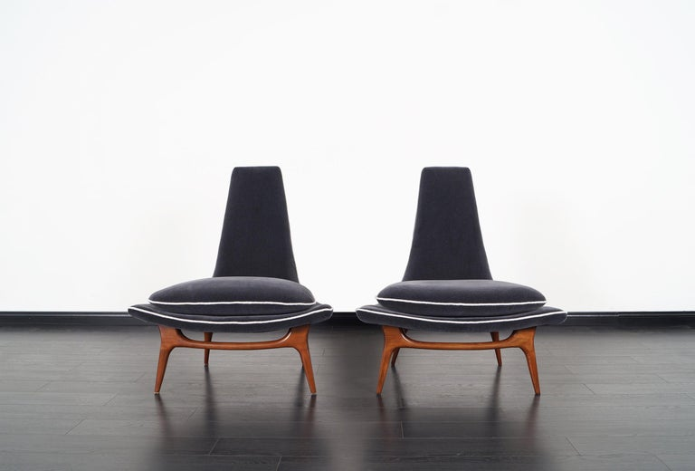 Stunning pair of vintage high back lounge chairs designed by Karpen of California, circa 1950s. These magnificent chairs feature sculpted solid walnut legs that show smooth curves and graceful lines across the frame. They've been professionally