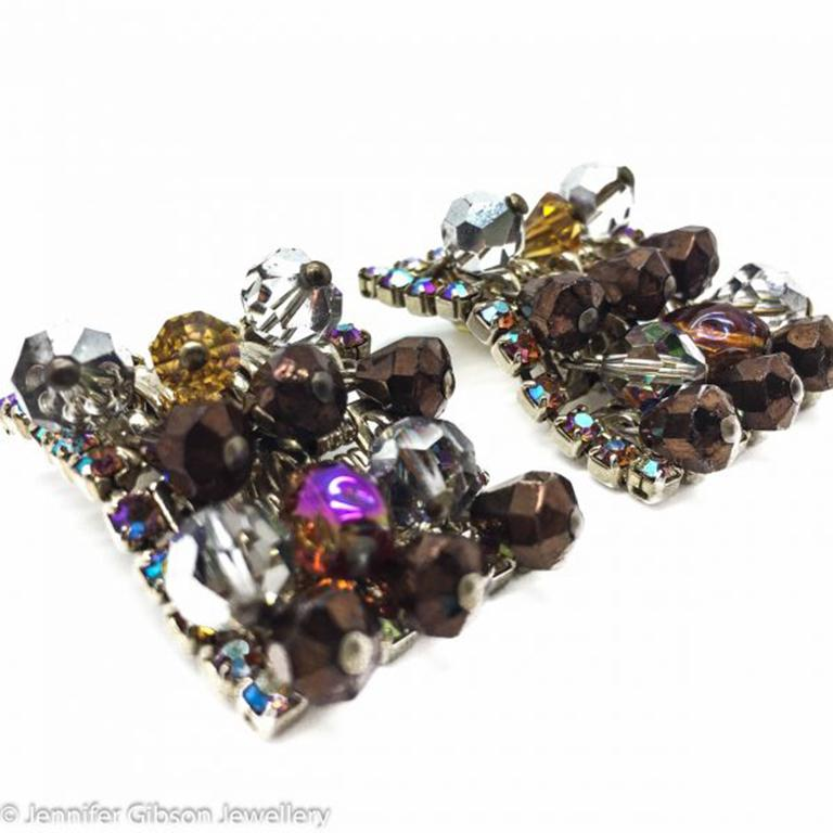 A fab pair of uber glam Vintage Hobe earrings from the mid-century. Rectangular, fully loaded articulated clips dripping with bead crystals in glorious shades of metallic brown, grey and amber. An aurora borealis finish projects a pink and orange