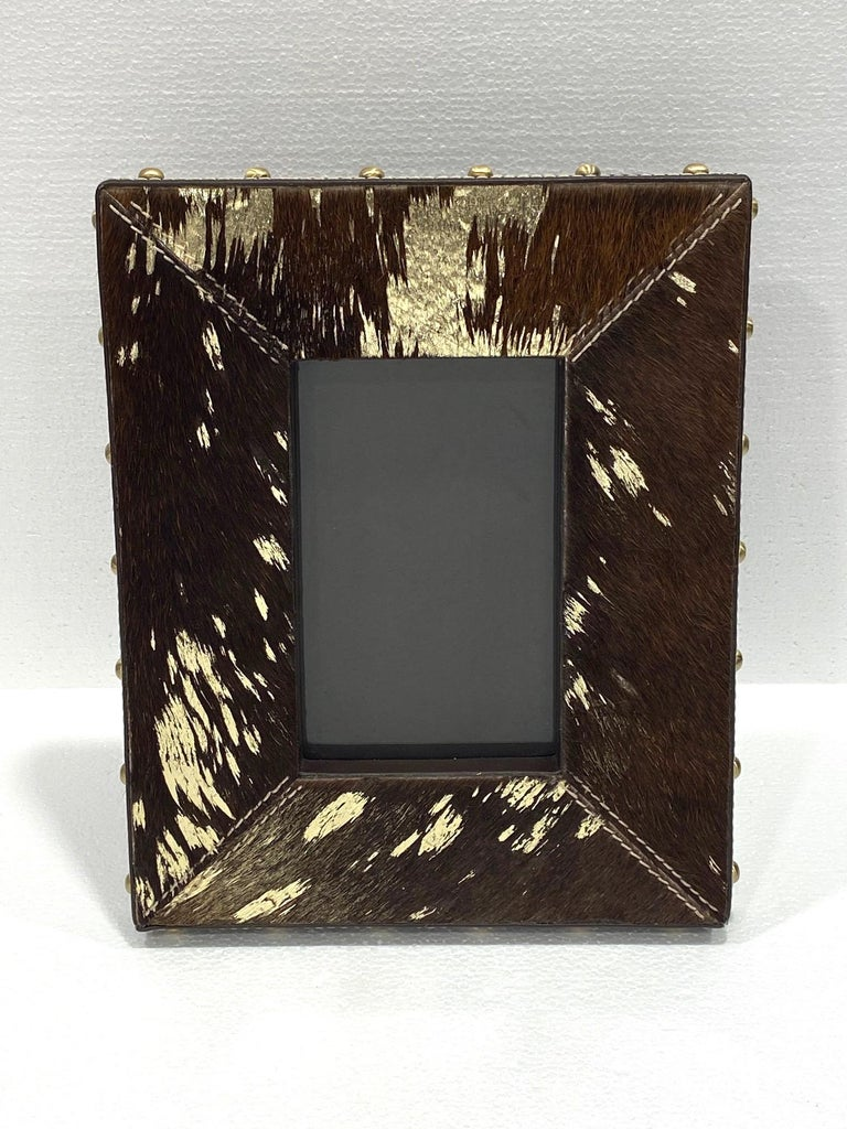 Rustic Hollywood Regency photo frame in dark brown cowhide with gold metallic foil accents. Handcrafted with brown leather trim and brass studs along the borders. Frame features handstitched details and holds 4