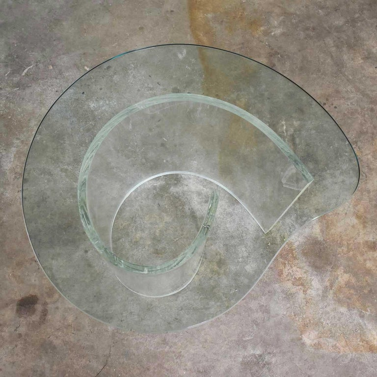 Striking vintage Hollywood Regency Lucite snail or spiral end or side table with a kidney shaped glass top. The Lucite is in wonderful condition clear and with only small minor age appropriate scratches. The fabulous kidney shaped glass