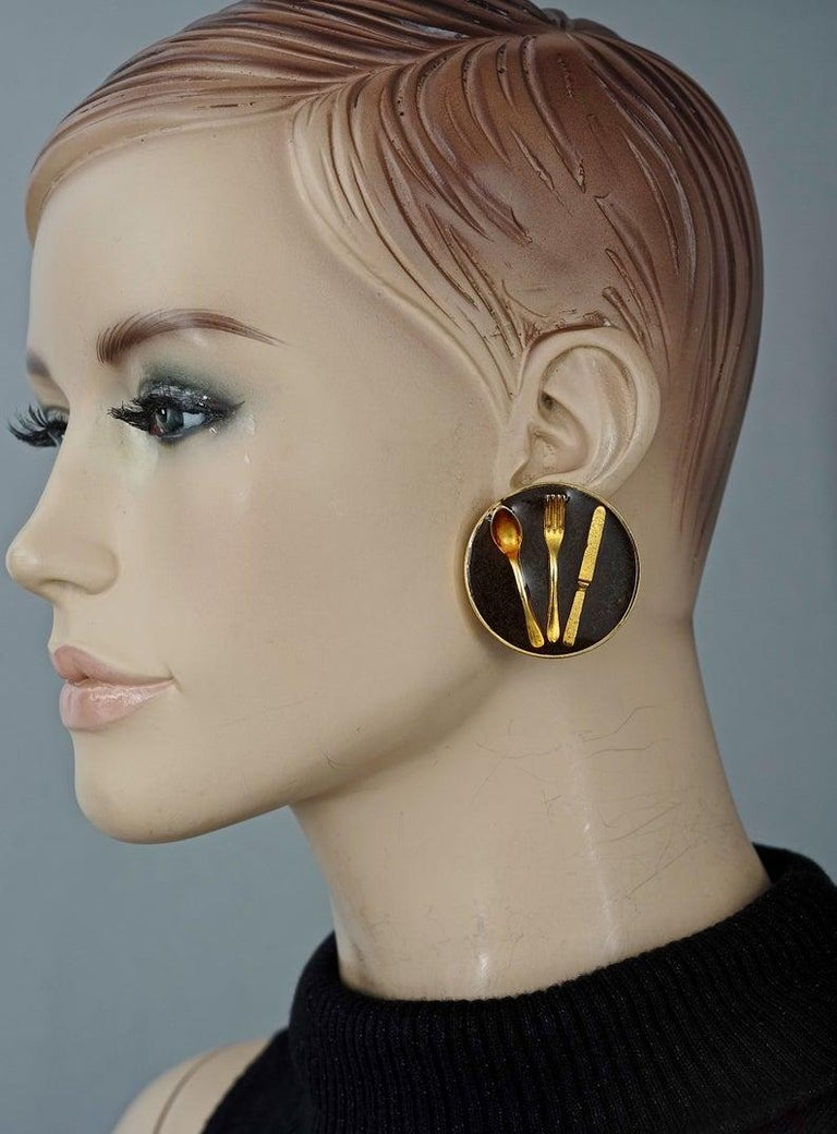 Vintage Iconic MOSCHINO Cutlery Earrings  Measurements: Height: 1.57 inches (4 cm) Width: 1.57 inches (4 cm) Weight per Earring: 23 grams  Features: - 100% Authentic MOSCHINO. - Massive black resin disc earrings with embedded cutleries. - Gold tone