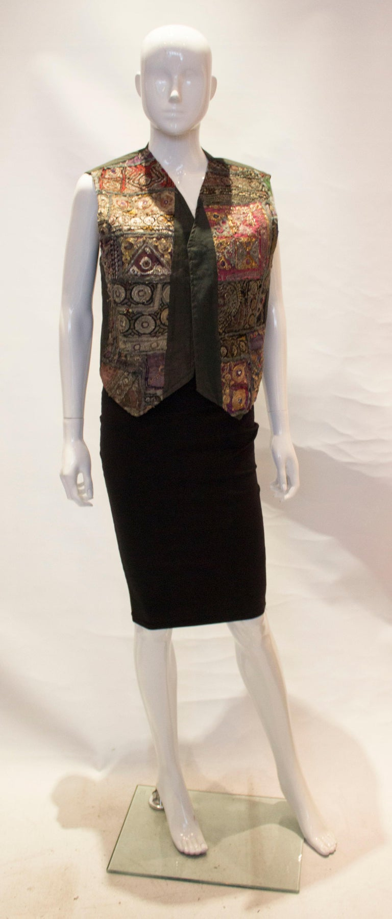 A fun and east to wear vintage Indian waistcoat. The fabric is a grey cotton with decoration on the front.