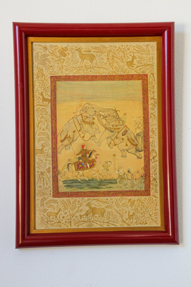 Vintage Indian miniature painting in red wood frame. The painting tells a story, very fine art work in hand-painted watercolors gouache on paper. Indian Mughal school style miniature painting by an Indian artist. The scene is two elephants battling