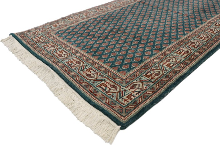 72083, vintage Indian runner with Old World Victorian style. This hand knotted wool vintage Indian runner displays an all-over repetitive pattern of opulent boteh motifs. The widely used boteh motif is thought to symbolize life with its resemblance