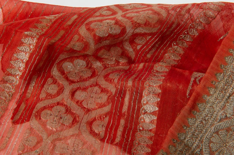 Vintage Indian sari in a beautiful coral color, with floreal patterns and a rich border. It has been worn, therefore there are some stain, even if washed. Some sari are in silk, other in synthetic blend - It may be an idea for evening dress or