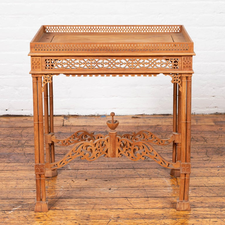 A vintage Indonesian carved side table from the mid-20th century, with open fretwork design and cross stretcher. Our attention is immediately drawn to this side table's intricate carving. Featuring a rectangular tray top surrounded by a pierced