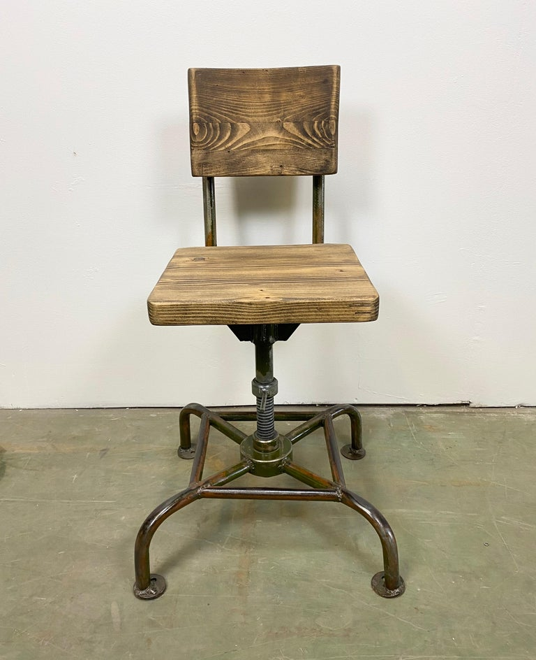 This industrial chair was made in former Czechoslovakia during the 1950s. It features an iron construction and a wooden seat and backrest. The chair is in very good vintage condition. Weight of the chair is 16 kg.