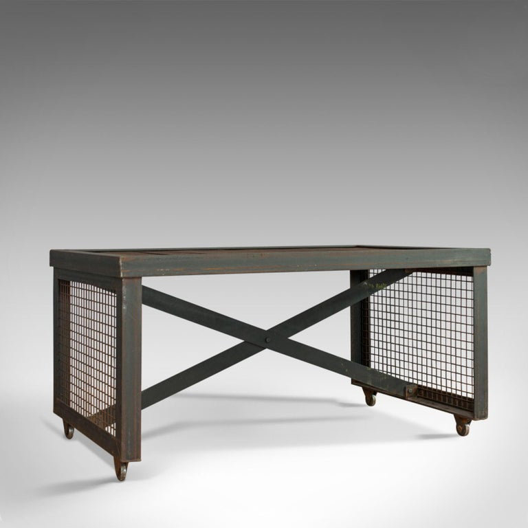 This is a vintage industrial coffee table. An English, foundry steel and oak table dating to the 20th century.   Strong industrial taste with a desirable aged patina Select cuts of weathered oak display a fine grain interest Rich, dark hues