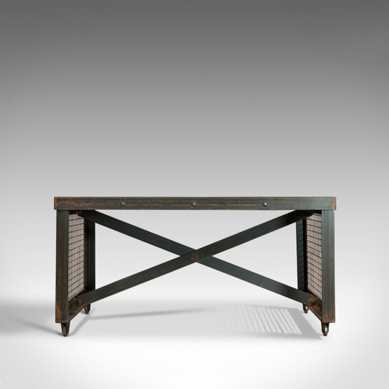 This is a vintage industrial coffee table. An English, steel and oak table dating to the 20th century.  Strong industrial taste with a desirable aged patina Select cuts of weathered oak display a fine grain interest Exposed welds at each corner