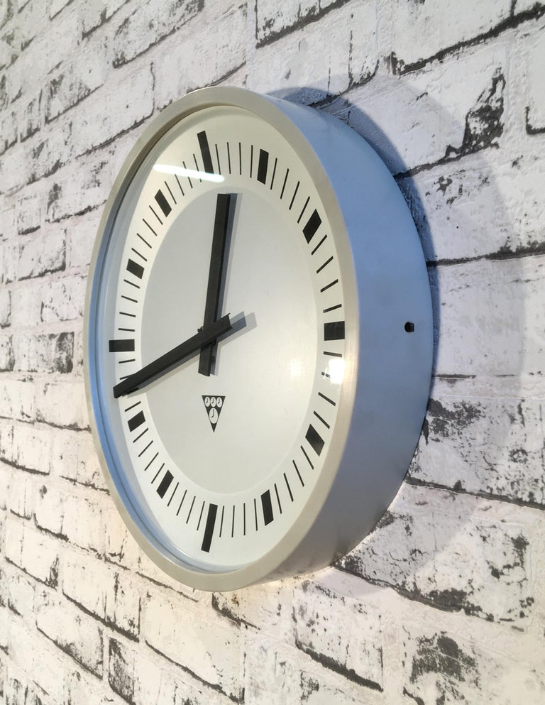 This wall clock was produced by Pragotron in former Czechoslovakia during the 1970s. It features a grey bakelite frame and a clear glass cover. The piece has been converted into a battery-powered clockwork and requires only one AA-battery.
