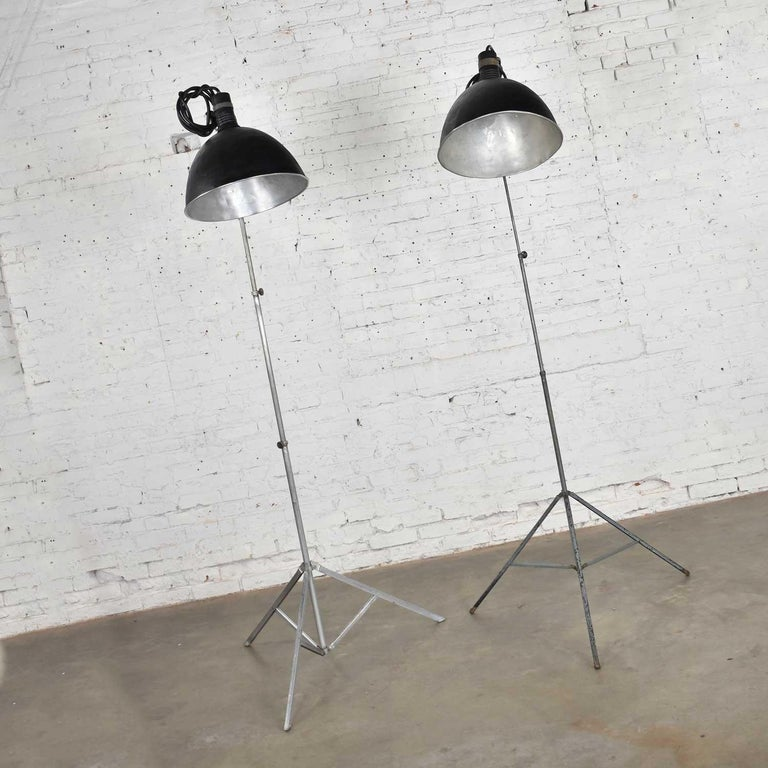 Fabulous vintage Industrial pair of aluminum and steel structured photographers floor lights with tripod bases. They are in wonderful vintage condition Beat up with lots of dents and patina. Fresh coat of texture paint on shades. Please see photos.