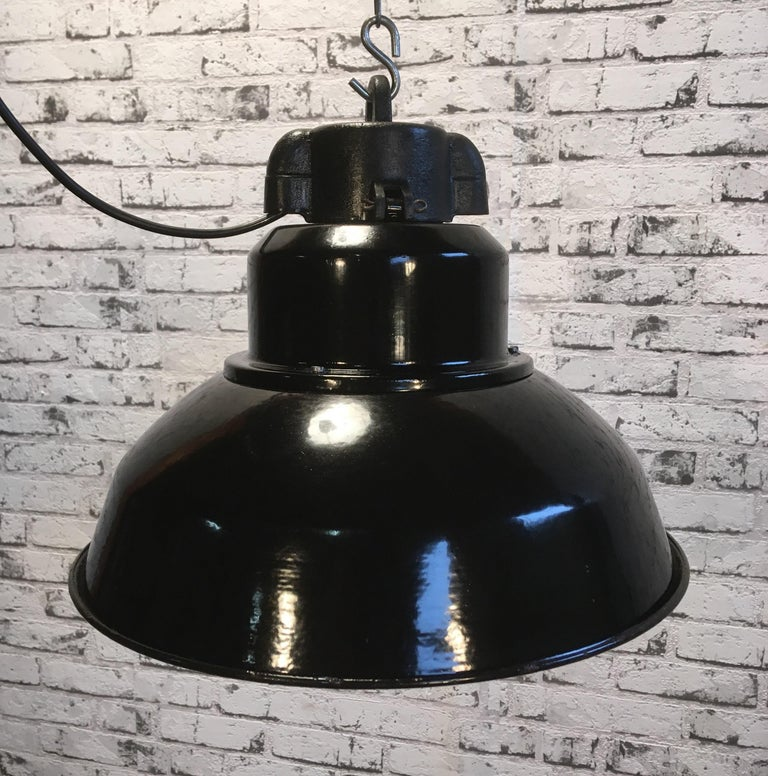 This industrial style pendant lamp was produced in former Czechoslovakia during the 1960s It features black enamel shade with white interior and cast iron top. New porcelain socket for E 27 lightbulbs and wire.