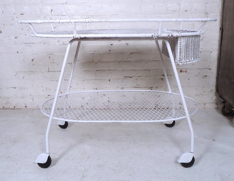 Unique vintage modern two-tier tea cart featuring a painted white metal frame, wicker top, and set of four wheels.