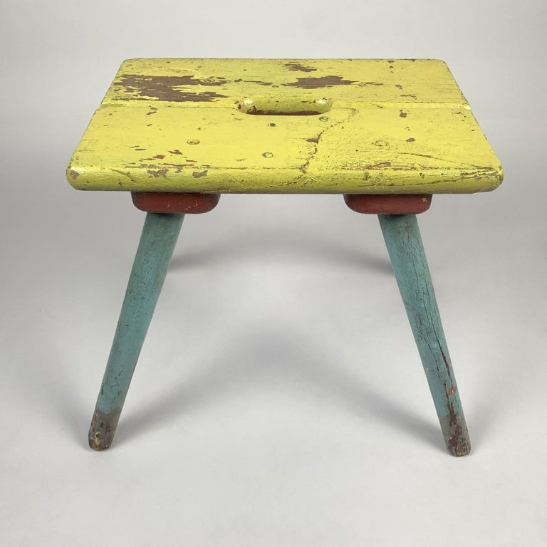 This unique vintage colorful wooden stool with original paint and naturally aged patina has a lot of character. The original chippy paint has been sealed. Even though it's legs look pretty worn out, it's still stable and ready to brighten up your
