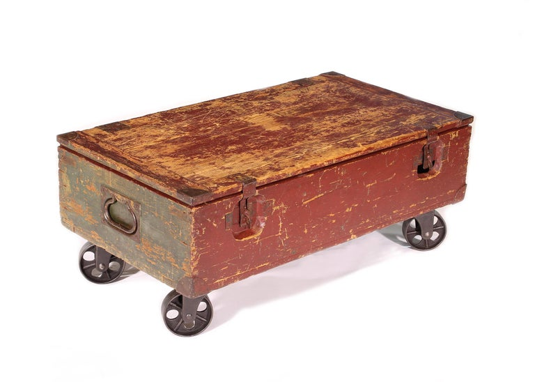 Authentic vintage distressed coffee table made of a wooden storage trunk and antique castors. Measures: 41