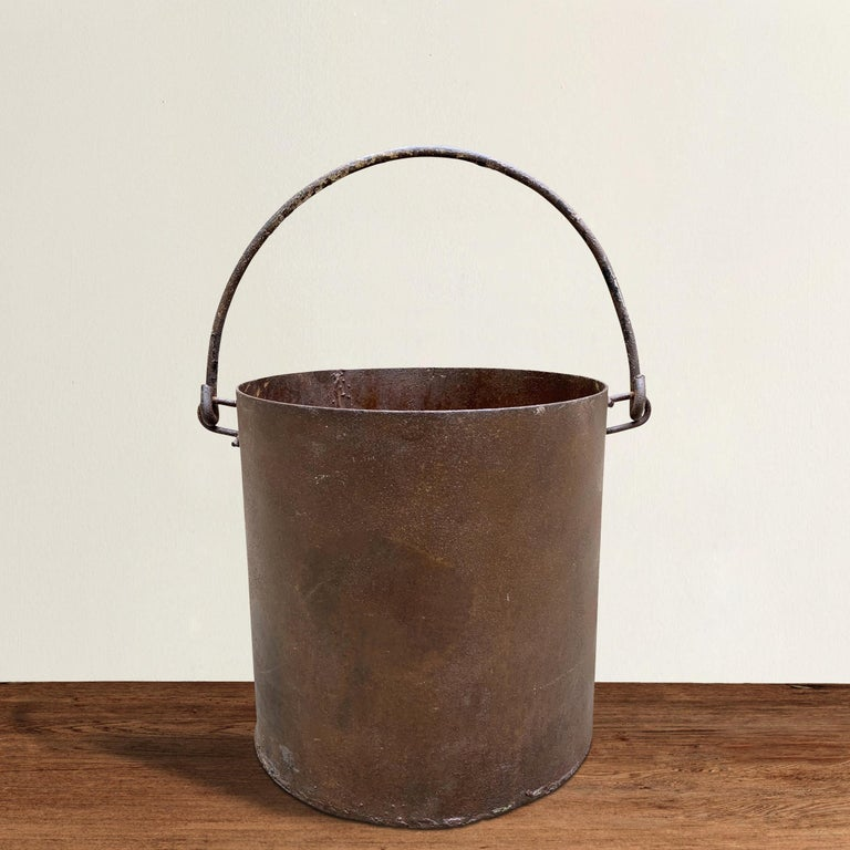 A stoic vintage iron bucket with a curved handle, and perfect for use as a waste paper basket in your powder room, office, or filled with ice and used to chill wine at your next fête.