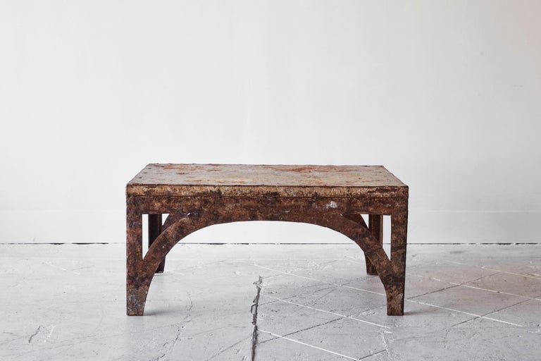 This industrial iron coffee table features arched legs and a perfectly chipped paint and rust finish that only time can bestow. This table is the perfect coffee table for any room.