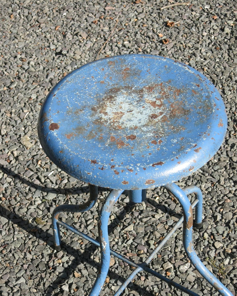 Vintage medical stool painted blue with losses and rust. It raises from 18