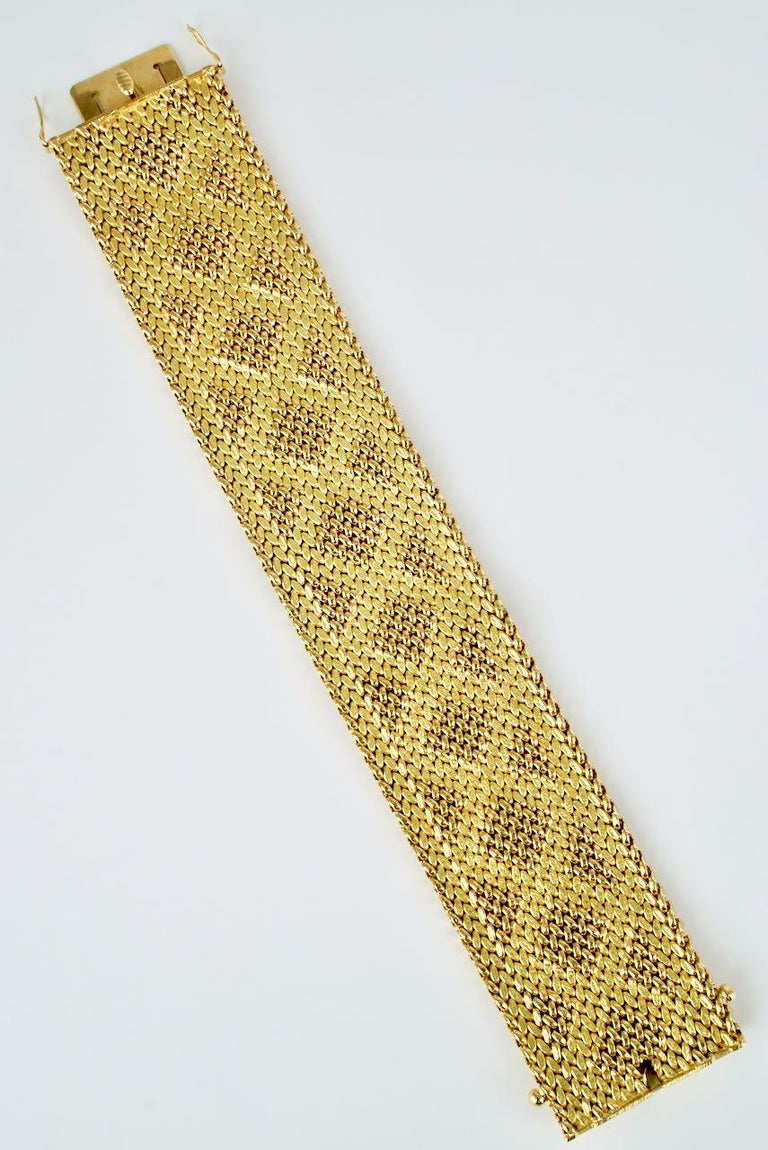 A beautifully executed bracelet of a wide 18k yellow gold mesh design that has then been rolled or stamped to produce a fabric like effect of a geometric pattern of shiny stitch or bead like links above a matt ground. Finished with an integrated box