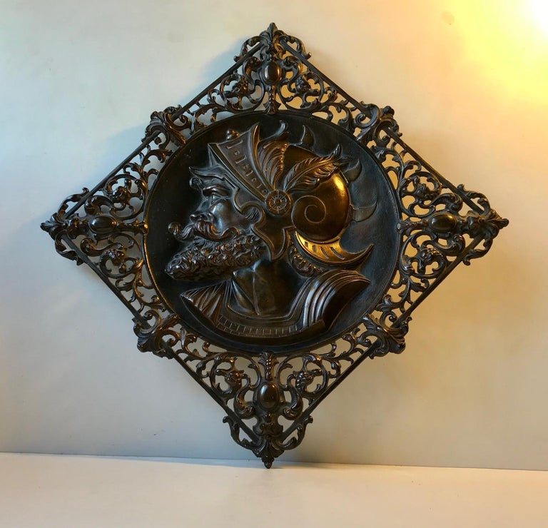 Whether this bronze wall plaque depicts a Roman Gladiator or Legionaire is uncertain. It was brought home from Rome in 1970 or 71. It is made from solid bronze that has a rich brown patina. The detailed ornamentation is partially perforated. It has