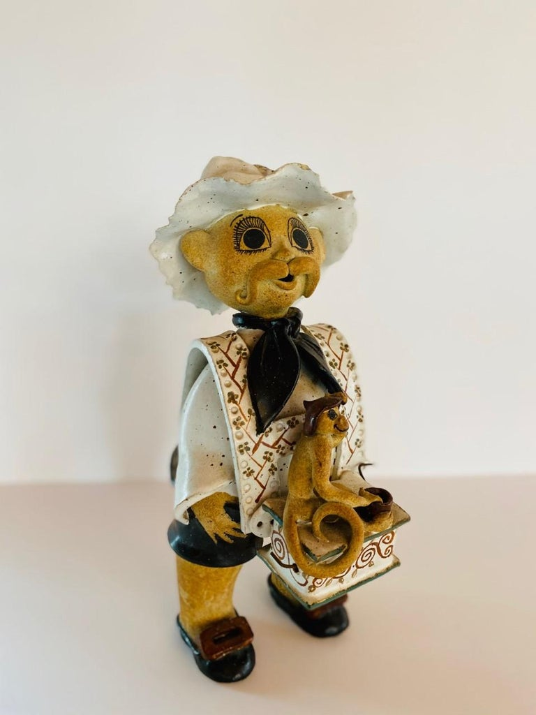 Beautifully rendered ceramic figure of man with musical grinding box and monkey. The detail and execution of this ceramic piece, made by hand is outstanding. The figure renders details (feather in hat, buttons in the back, and monkey figure