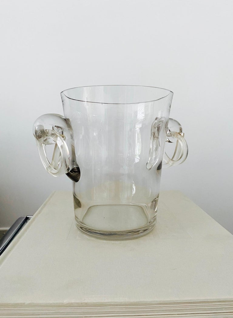 Italian Mid-Century Modern crystal ice bucket or champagne cooler with stylized pretzel handles in lucite. The cooler has a slight tapered form with horizontal fluted details and features blown glass scrolls on either side. All handcrafted with