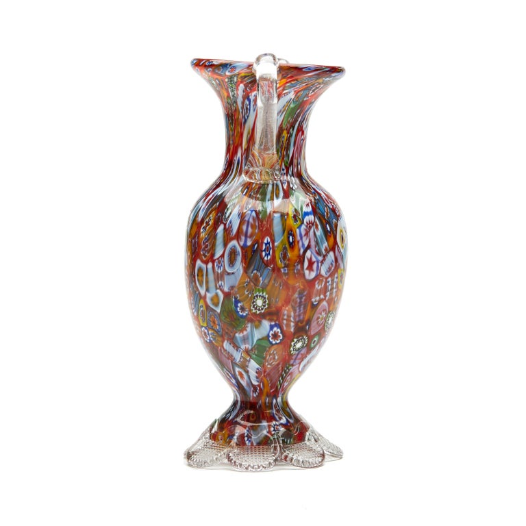 A stylish vintage Italian Murano twin handled millefiori vase by Fratelli & Toso. The hand blown glass vase stands on a clear glass petal shaped foot each impressed with a grid pattern from beneath supporting a bulbous shaped body with a narrowing
