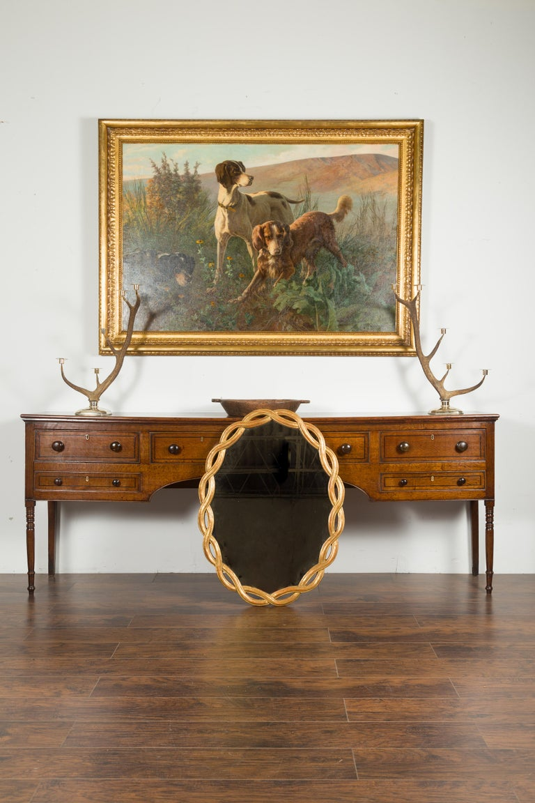 An Italian vintage giltwood oval mirror from the mid-20th century, with intertwining motifs. Created in Italy during the midcentury period, this oval mirror features a graceful intertwining frame surrounding a clear mirror. Showcasing a lovely red