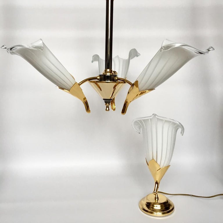 Gold and nickel-plated metal stem, gilt brass and white Murano art glass Calla Lily shades, three bulbs. Attributed to Franco Luce. Ceiling lamp - H 46 cm, D 62 cm Table lamp - H 40 cm, D 14 cm.