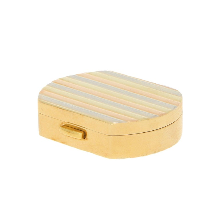 A vintage Italian pill box in 18-karat tricolour gold, circa 1990. This pill box of a cushion design features banded accents to the lid and base in a repeated pattern of alternating white, yellow and rose gold, the sides and aperture button in