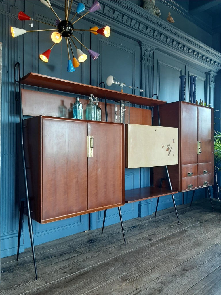 Vintage Italian livingroom furniture by Silvio Cavatorta with bar cabinet, storage space, bookshelves and bar. This Mid-Century Modern design wall unit / sideboard /buffet /bookcase is made in the 1960s. Made of teak veneerd wood, with brass handles
