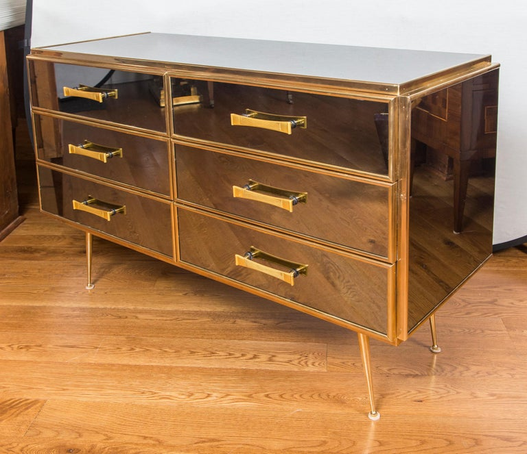Wonderful vintage six-drawer dresser in a tinted very light grey mirrored finish with brass detailing that is gold plated and finished with beautiful gold plated brass reeded pulls Note: unlike the usual mirrored furniture this one is quality