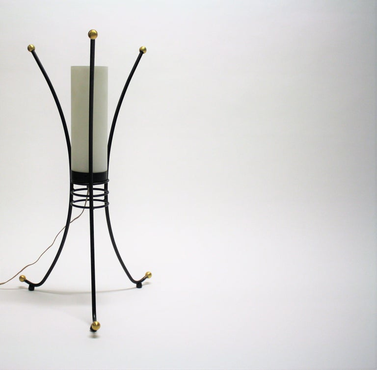 Charming tripod design mid century table lamp with a milk glass lamp shade.  The lamp has golden feet and tops.  Designer unknown.  The lamp can be used as a small floor lamp or as a large table lamp.  It emits a warm and welcoming