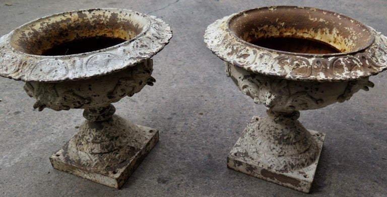 This vintage pair of Victorian solid cast iron garden urn shape planters date from the late 19th century. This exceptional pair of original planters were produced by J W Fiske & Company of New York City. Featured around the body of each are four